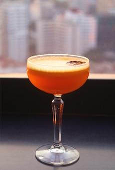 Bicchiere di vivace cocktail arancione sulla terrazza sul tetto con vista urbana sfocata sullo sfondo