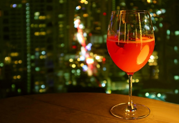 Bicchiere di cocktail rosso vivo isolato sul tavolo delle terrazze sul tetto con vista notturna urbana sfocata