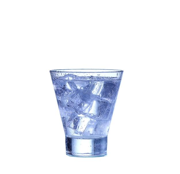 Bicchiere d'acqua, ghiaccio e fetta di limone fresco su una parete bianca