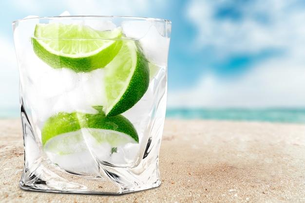 Bicchiere d'acqua e lime sullo sfondo
