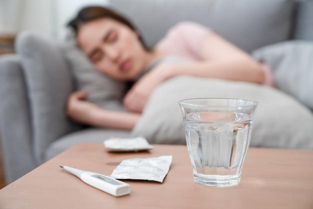 Bicchiere d'acqua, pacchetto di pillole e termometro digitale sul tavolo con la donna asiatica malata che si trova sul cuscino del divano dopo aver preso le medicine