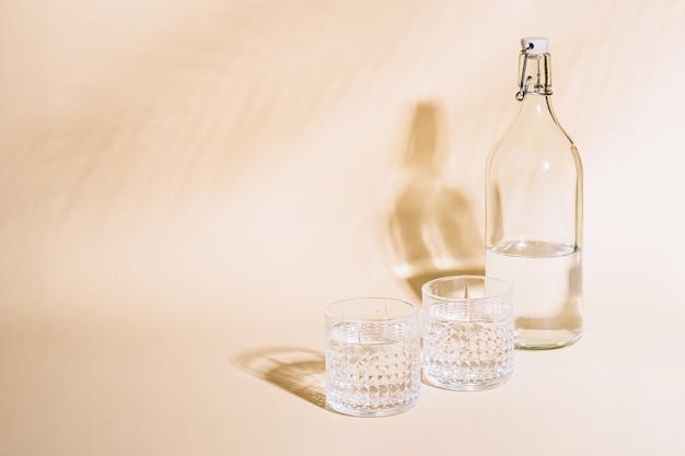 Bicchiere d'acqua su pastello vicino alla bottiglia