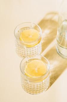 Bicchiere d'acqua sulla parete pastello vicino alla bottiglia