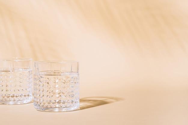 Bicchiere d'acqua su pastello con ombra dura