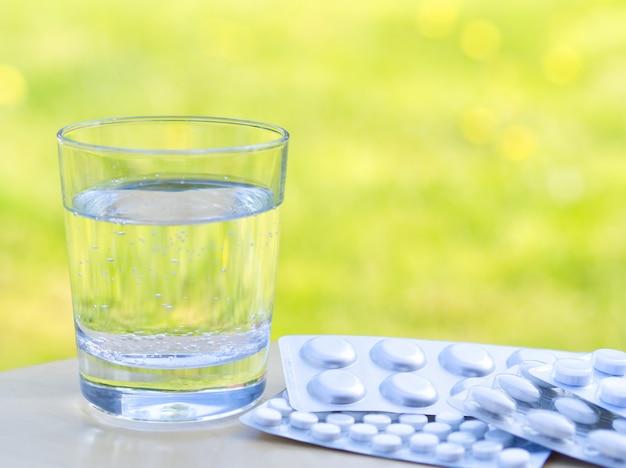 Bicchiere d'acqua e delle pillole sulla tavola sul fondo verde della natura. allergico a fiori e polline