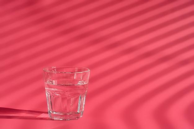 Bicchiere d'acqua su carta rossa luce solare intensa, preparato per l'assunzione di polvere di collagene.