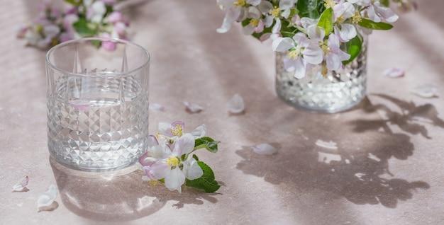 Bicchiere d'acqua sul tavolo con un ramo di melo in fiore in un bicchiere