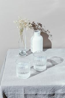 Bicchiere d'acqua e vaso con fiori