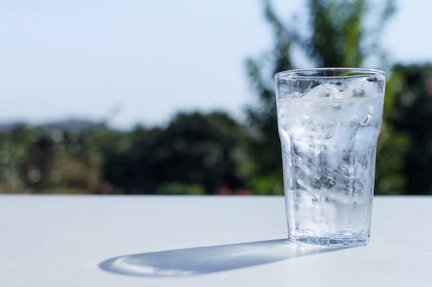 Un bicchiere d'acqua con ghiaccio sul tavolo.