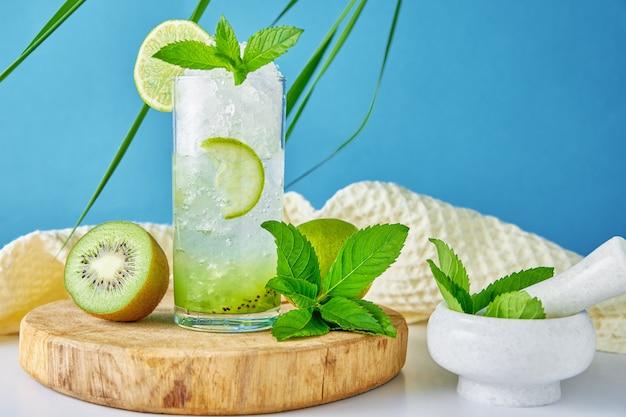 Bicchiere d'acqua con kiwi lime e menta su sfondo blu