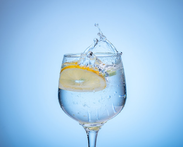 Bicchiere d'acqua con limone caduto e spruzzata su sfondo azzurro sfumato.