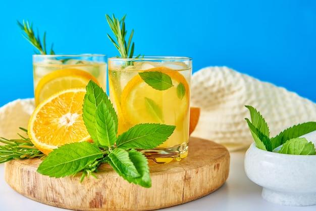 Bicchiere d'acqua con menta arancione e rosmarino su sfondo blu