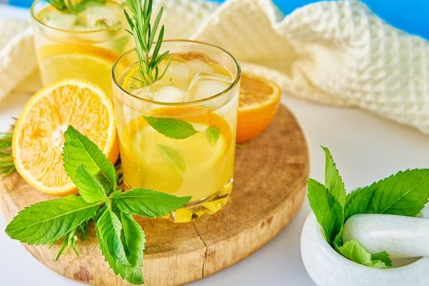 Bicchiere d'acqua con menta arancia e rosmarino