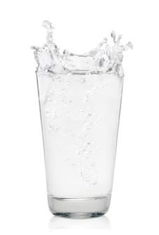 Bicchiere d'acqua con splash close-up su uno sfondo bianco. isolato