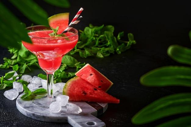 Bicchiere di cocktail margarita di anguria con menta e ghiaccio. bevande rinfrescanti estive in bicchieri sul tavolo nero. concetto di sana alimentazione estiva.
