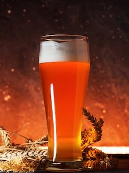 Un bicchiere di birra di frumento illuminato da una luce gialla su uno sfondo scuro