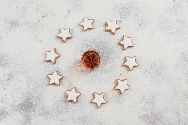 Un bicchiere di whisky o bourbon e biscotti a stella cerchio su sfondo bianco. concetto di umore del whisky invernale