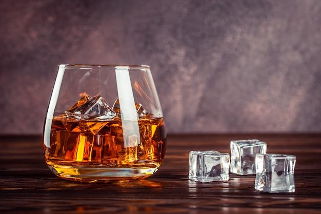 Un bicchiere di whisky da vicino. brandy con ghiaccio su un tavolo di legno marrone. cognac, bourbon. bevanda alcolica forte. bevanda alcolica gialla trasparente.