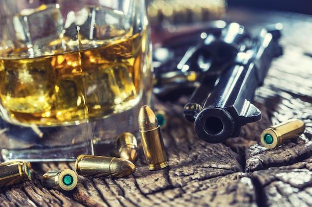 Bicchiere di whisky cognac o bourbon con revolver e proiettili accesi