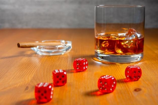 Bicchiere di whisky con cubetti di ghiaccio e posacenere con sigaro. dadi rossi su un tavolo di legno