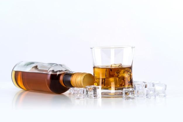 Bicchiere di whisky con cubetti di ghiaccio e bottiglia su sfondo bianco