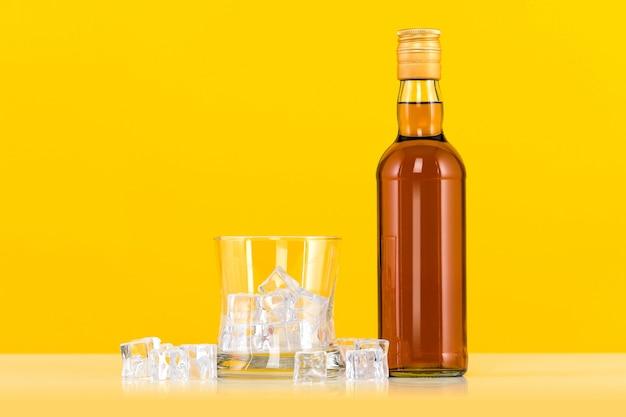 Bicchiere di whisky con cubetti di ghiaccio e bottiglia su sfondo giallo
