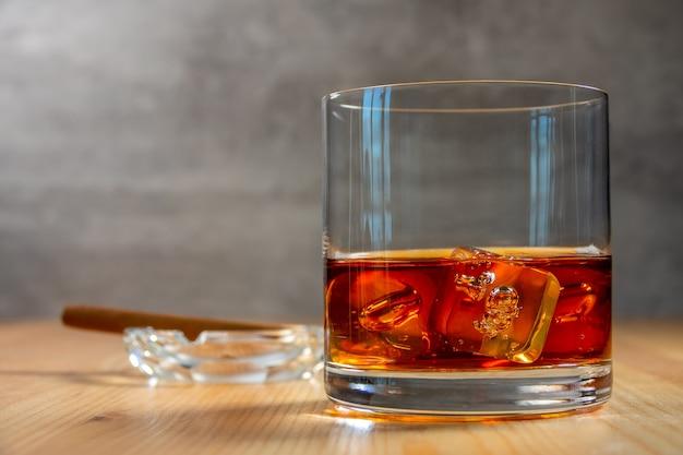 Bicchiere di whisky con cubetti di ghiaccio sul tavolo di legno. un posacenere con un sigaro sfocato
