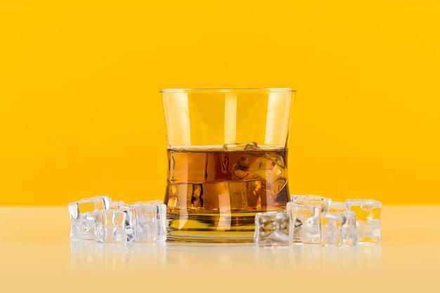 Bicchiere di whisky con cubetti di ghiaccio su sfondo giallo