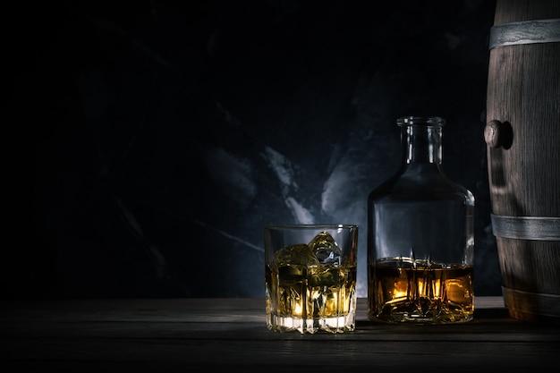 Bicchiere di whisky con ghiaccio, decanter e una botte di legno