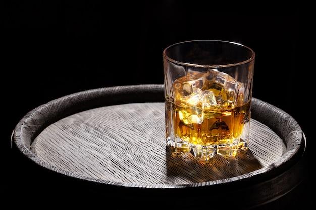 Bicchiere di whisky con ghiaccio sul barilotto di legno
