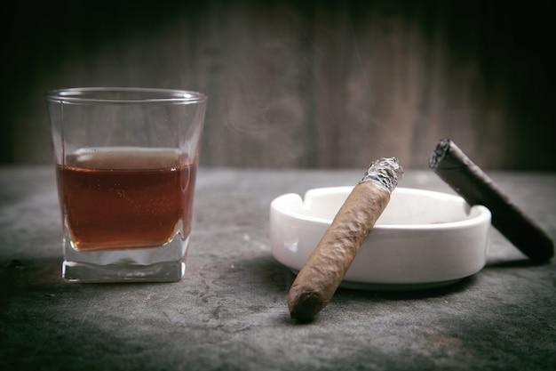 Bicchiere di whisky, posacenere e sigari sul tavolo.