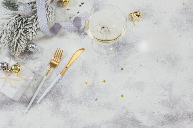 Un bicchiere di spumante bianco o champagne e decorazioni per il nuovo anno su sfondo chiaro. concetto di vacanze invernali. vista dall'alto con copia spazio per il testo