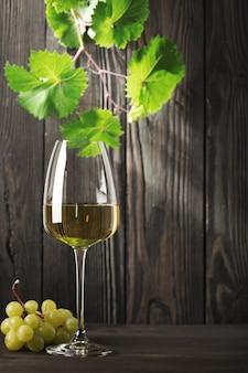 Un bicchiere di vino bianco e un grappolo d'uva su un vecchio tavolo di legno. sfondo scuro.