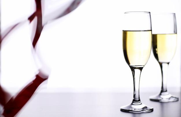 Bicchiere di vino bianco su un tavolo su uno sfondo bianco isolare