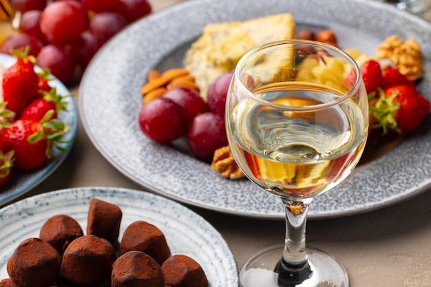 Bicchiere di vino bianco, cioccolatini al tartufo e fragola da vicino