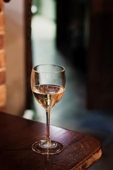 Bicchiere di vino bianco sulla tavola di legno d'epoca