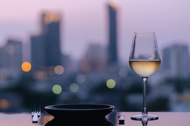 Un bicchiere di vino bianco con piatto con sfondo di luci della città.