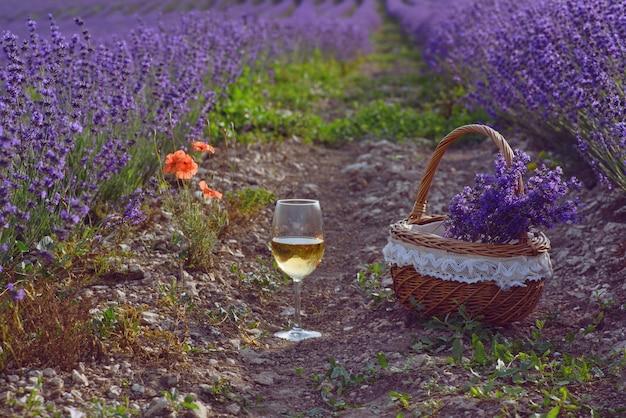 Bicchiere di vino e cesto nel campo di lavanda