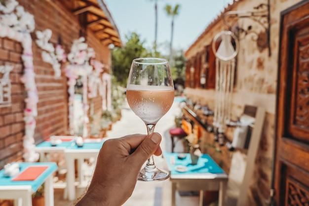 Bicchiere di vino in mano un bicchiere di vino rosato fresco sullo sfondo di un caffè estivo in un me...