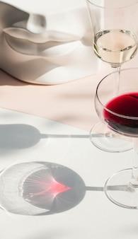 Bicchiere di vino nella luce dura con belle ombre lunghe su bianco