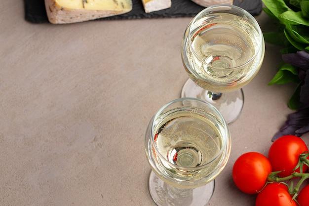 Bicchiere di vino e un pezzo di formaggio sul tavolo vicino foto