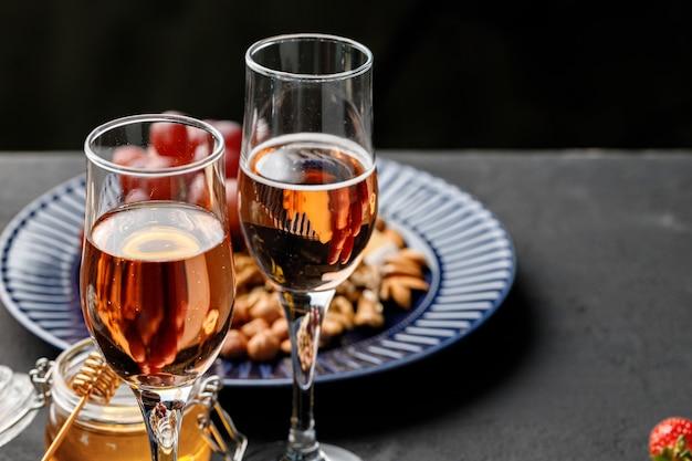 Bicchiere di vino e piatto con noci sulla tavola nera si chiuda
