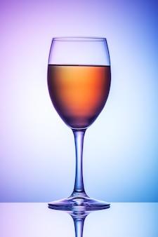 Un bicchiere di vino si trova su un tavolo su uno sfondo blu-viola.