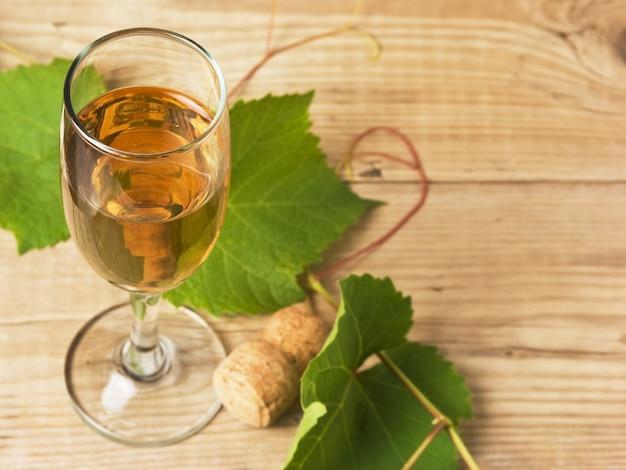 Bicchiere di vino e vite su un tavolo di legno