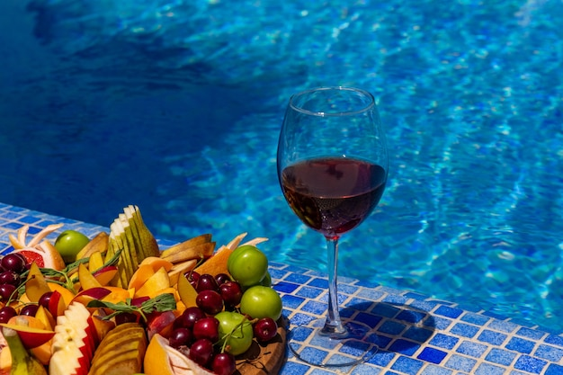 Un bicchiere di vino con fette di frutta a bordo piscina