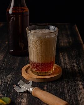 Vetro con birra e una bottiglia di birra su un tavolo scuro