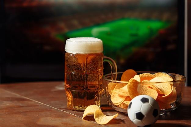 Vetro con birra e patatine. concetto di tifosi di calcio