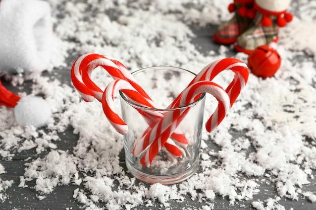 Bicchiere con bastoncini di zucchero natalizio e neve sul tavolo