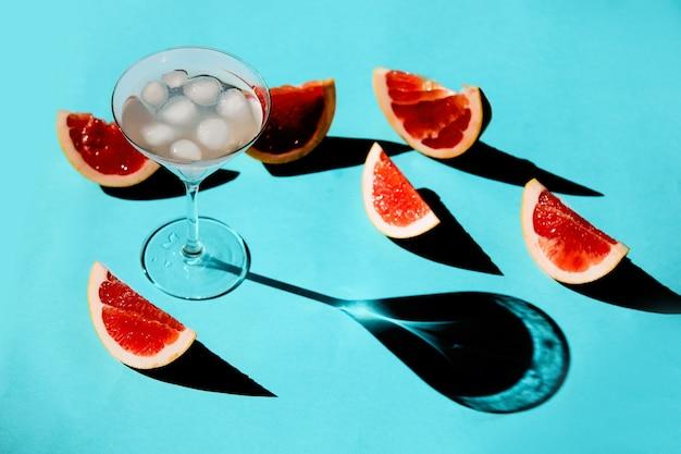 Bicchiere con cocktail e pompelmi tagliati intorno sulla superficie blu.