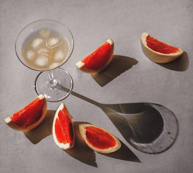 Vetro con cocktail e pompelmi tagliati intorno sulla superficie grigia.
